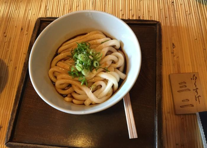 Bowl of thick udon noodles with green onion on top on brown tray with wooden chopsticks
