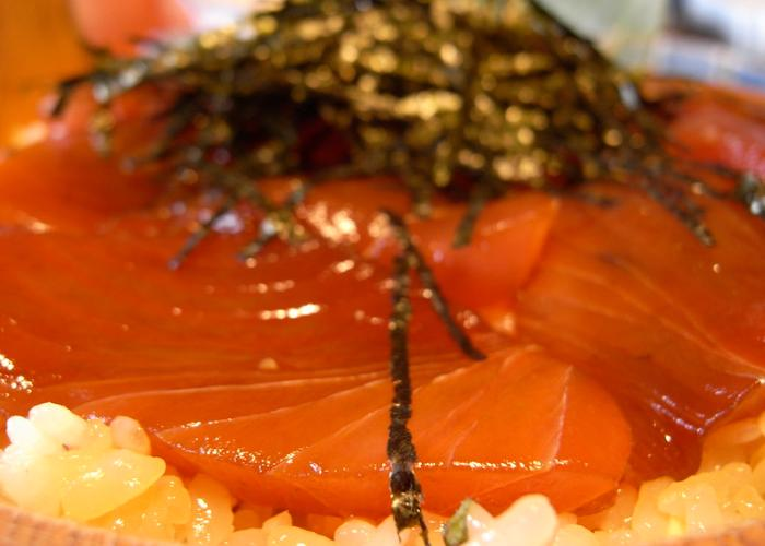 Close-up of rice with red tuna and seaweed shavings on top
