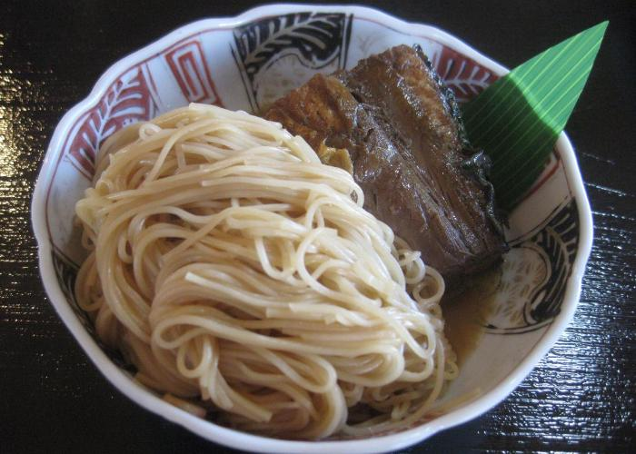 A bowl of yakisaba somen, with a portion of mackerel on a bed of noodles