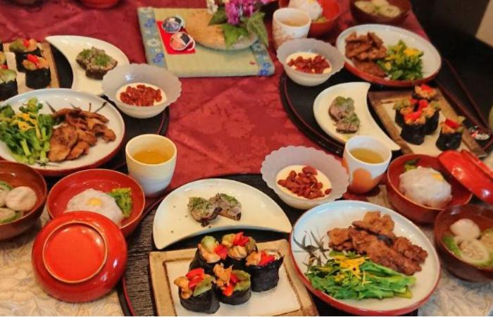 Table filled with food on different plates and dishes, including sushi, chicken, rice, vegetables