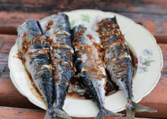 Four sardines with brown sauce and sesame seeds on white dish with flowers printed on it