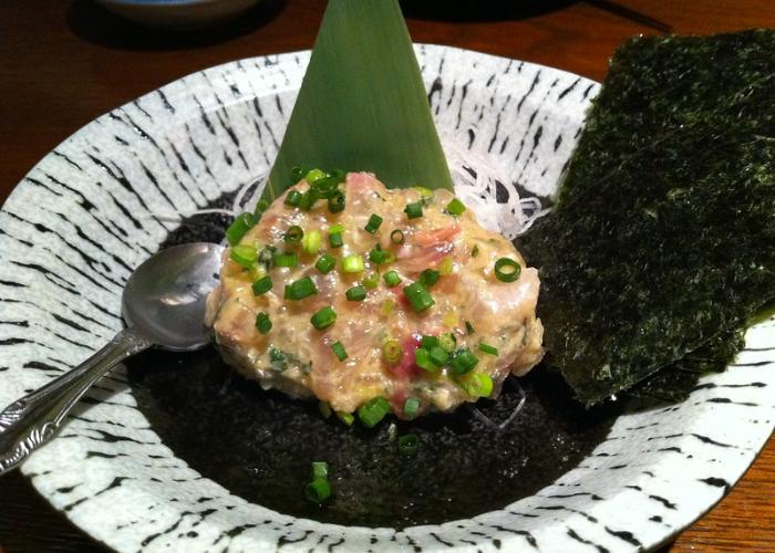 Clump of beige minced fish meat with soybean paste, topped with green onions, on top of seaweed with spoon