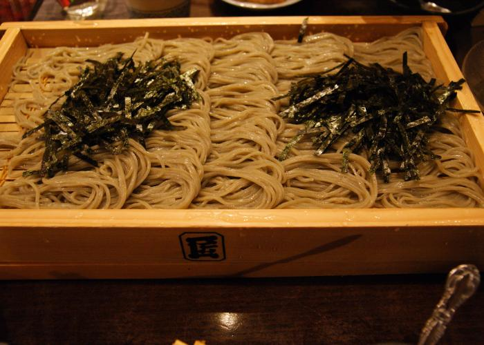 A square platter with bundles of cooked noodles arranged on top