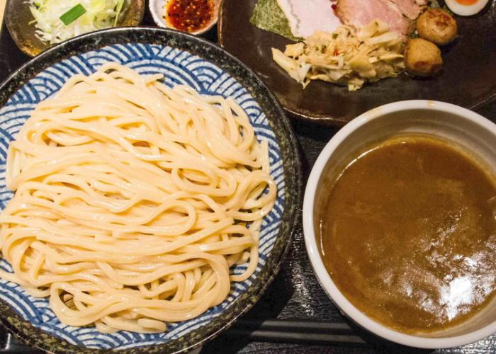 Blue dish of plain tsukemen noodles next to bowl of brown broth with other sides in background