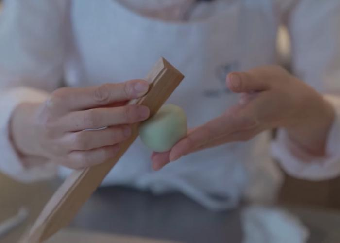 Hand using wooden stick tool to make indent in japanese wagashi dough