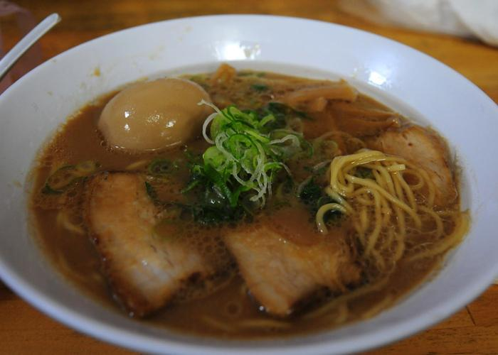 A bowl of Wakayama ramen with thick pork broth, strips of chashu, a whole boiled egg, and a topping of thinly-sliced negi
