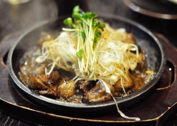 "Miyazaki Grilled Chicken a.k.a. ""jidori no sumibiyaki"" served on an iron plate"