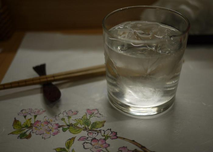 Glass of shochu on ice on a placemat decorated with sakura