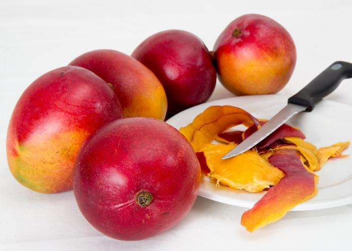 Mango with bright red skin next to a plate of sliced mango peels