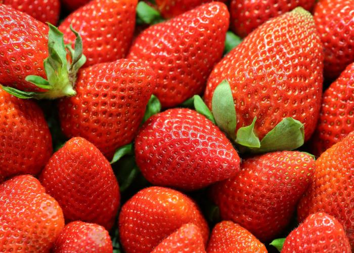 Bright red strawberries with leafy green tops