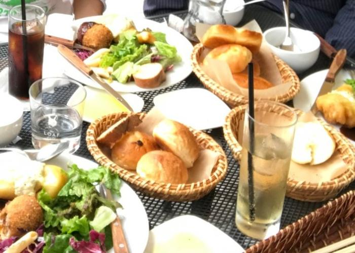 Spread of food, salad, bread, and pasta at The Loaf Cafe, an Osaka cafe with outdoor seating