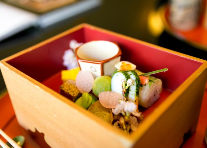 A close-up shot of delicate and colourful kaiseki cuisine in a wooden box
