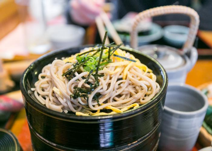 A close-up photograph of soba noodles at Honke Owariya, topped with strips of nori seaweed and light green spring onions