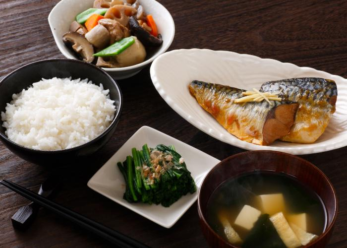 Japanese style breakfast with grilled fish, miso soup, rice, and veggie sides