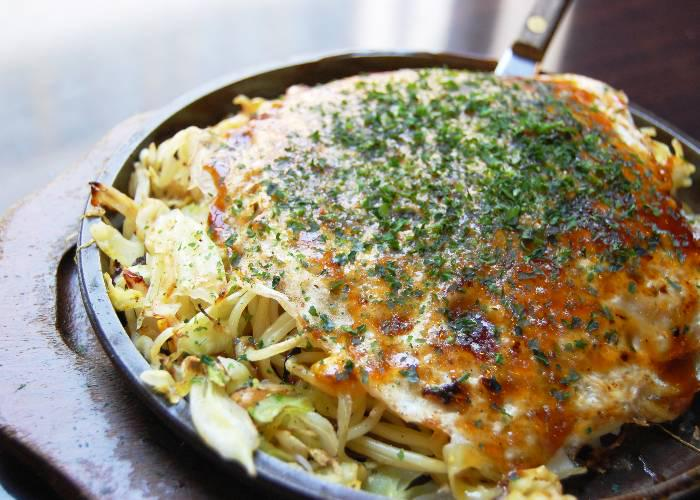 A big plate of Hiroshima okonomiyaki with noodles and seafood, topped by sauce and aonori