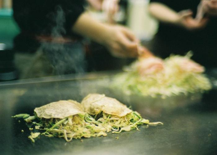 A smoking hot Hiroshima okonomiyaki, topped with vegetables, noodles and seafood, being cooked on an iron griddle