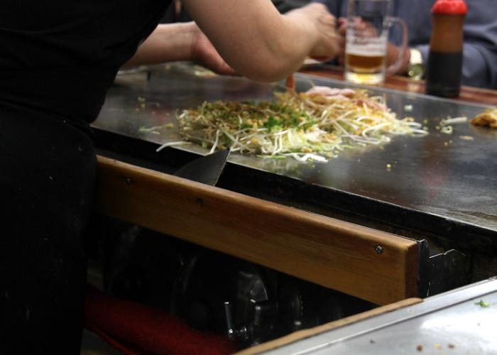A chef adding pork to the okonomiyaki, now filled with cabbage and tenkatsu