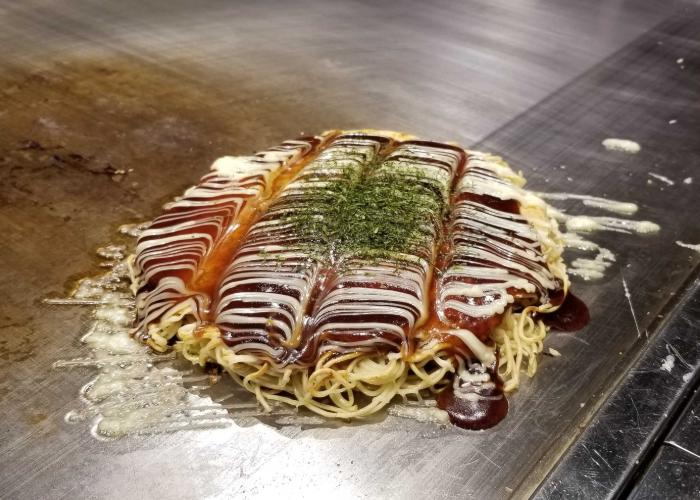 Classic Hiroshima-style okonomiyaki topped with Otafuku sauce, mayo, and a beautiful design
