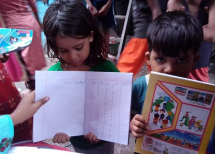 Schoolchildren hold up their homework assignments and books in India
