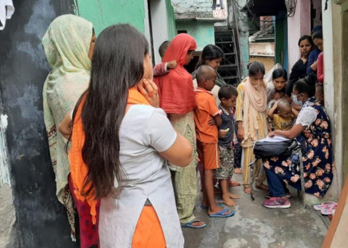 Schoolchildren in India gather around women who check their schoolwork