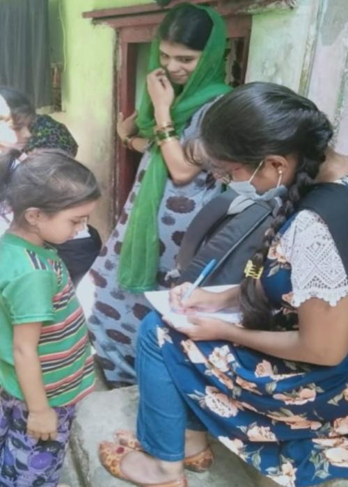 A woman checks a child's homework in India
