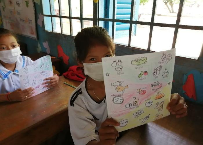 A student wearing a mask holds up a color coded picture with different food groups during a nutrition workshop by Nom Popok