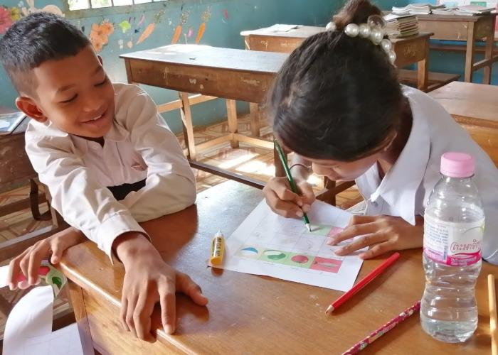 A Cambodian boy watches as a girl colors during a nutrition workshop