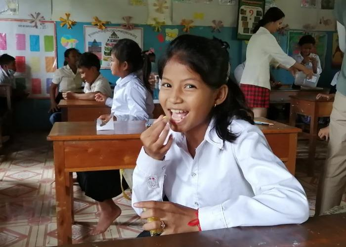 Cambodian girl eating a snack provided by Nom PoPok