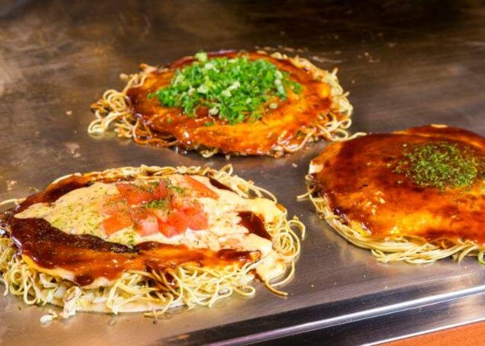 Three styles of Hiroshima okonomiyaki on a teppan, with soba noodles spilling out of the middle layer