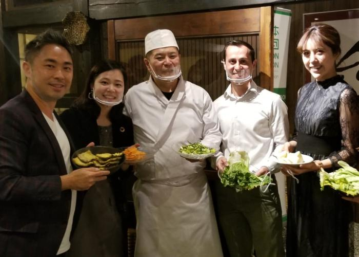 Chef Suzuki with the byFood and CRUST team at the sustainable dinner event holding up food scraps