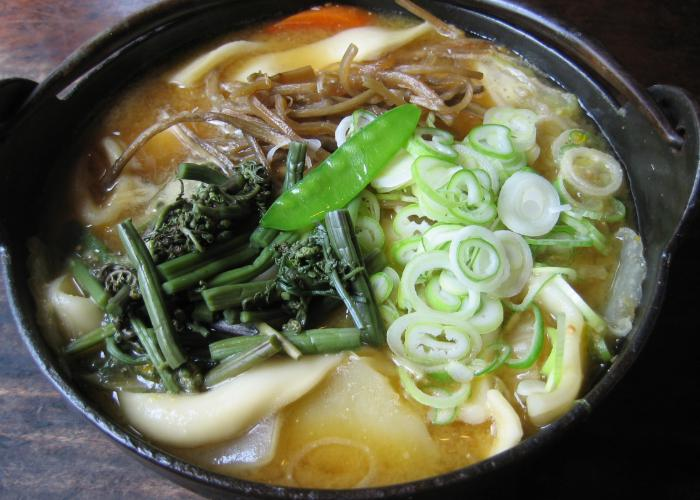 Close up image of a bowl of houtou noodles topped with vegetables