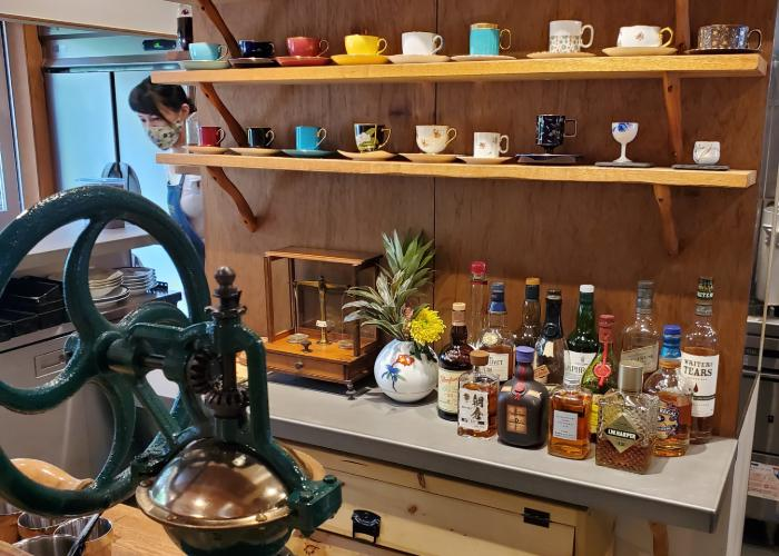 Interior at Cafe Rostro, a breakfast spot in Tokyo, showing open shelving with coffee cups