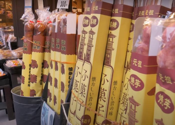 Barrels of giant sweet potato breadsticks being sold outside a store in Kawagoe