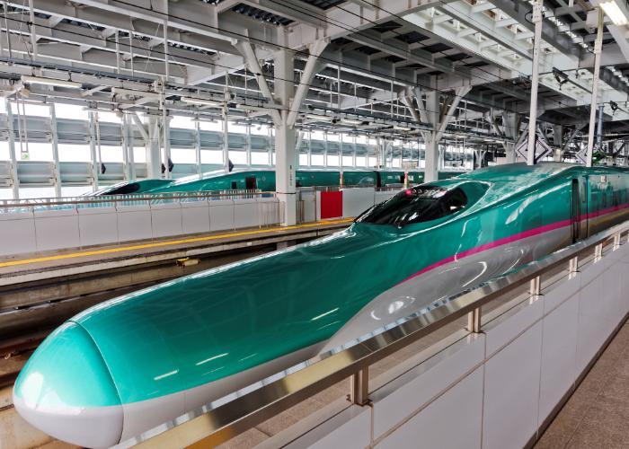 Vibrant green Tohoku Shinkansen waiting at a station platform