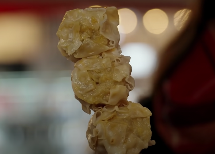Close up image of three shrimp shumai dumplings on a stick