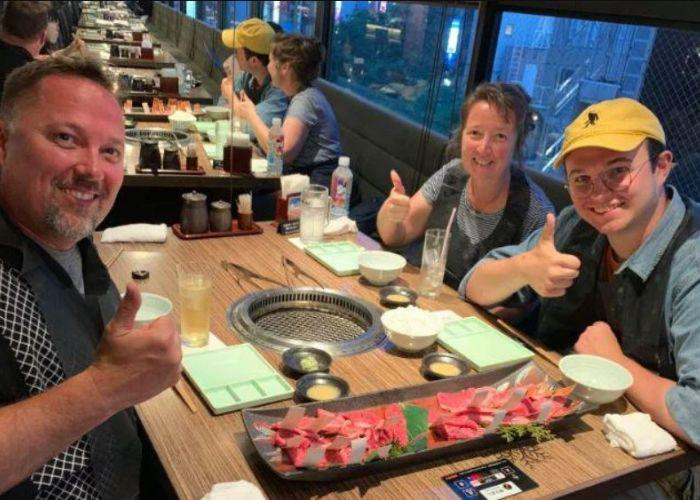 Family of three white people smiling and holding thumbs up around a yakiniku barbeque grill