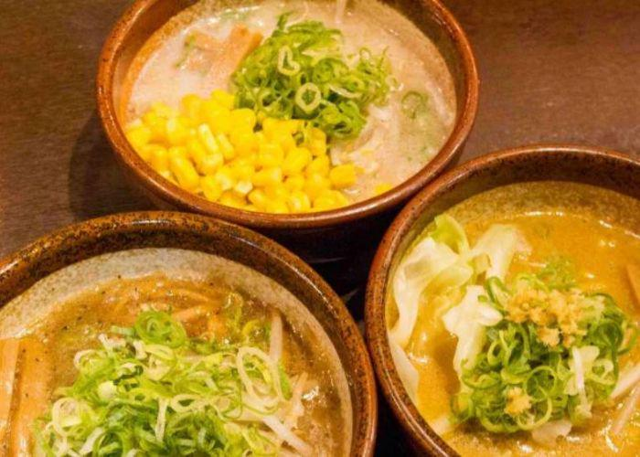 Three bowls of ramen with orange broth, topped with green onion, corn, and shredded garnishes