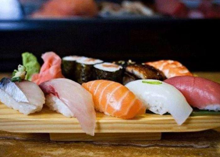 Five pieces of nigiri sushi of different bright colors on wooden platter with seaweed-wrapped rolls in background