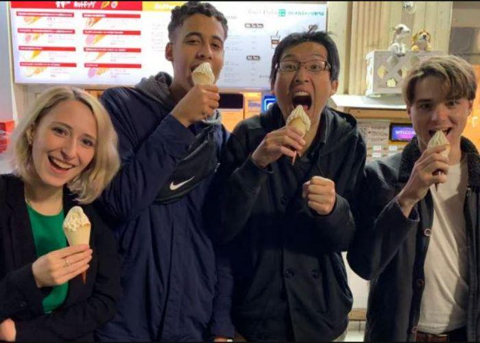 Four young people enjoying soft serve ice cream cones and making goofy faces at the camera