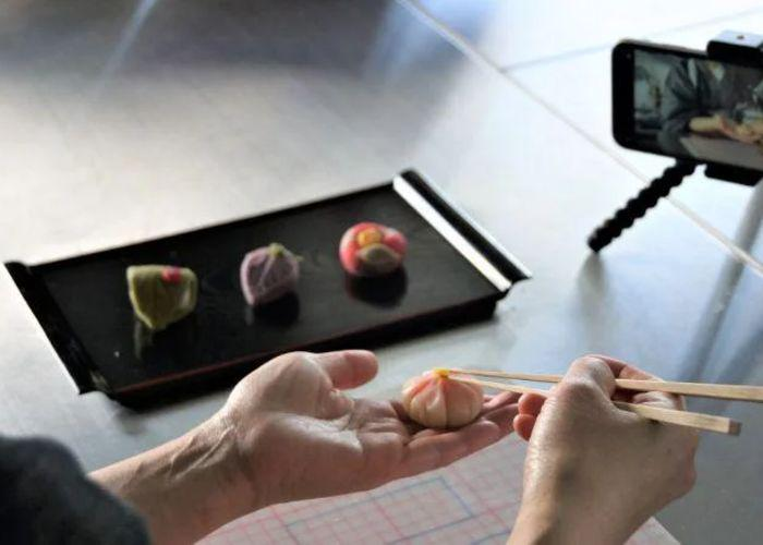 A tray of three wagashi sweets in the background, with a person's hands making another sweet and a smartphone on a stand filming it