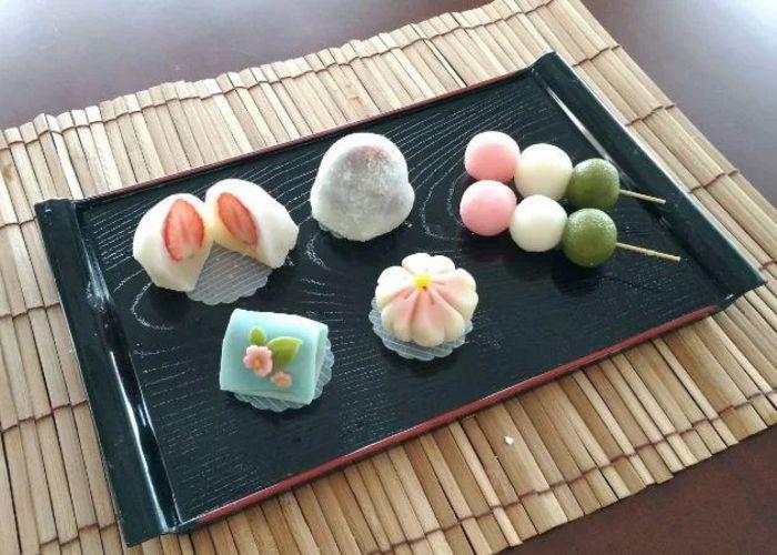 A tray of wagashi, including colorful dango, a flower-shaped sweet and ichigo daifuku, on a bamboo mat