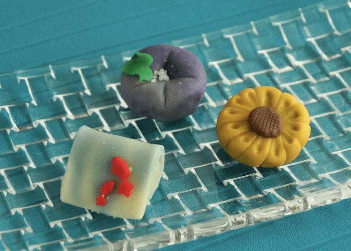 Three different colorful wagashi sweets on a blue background