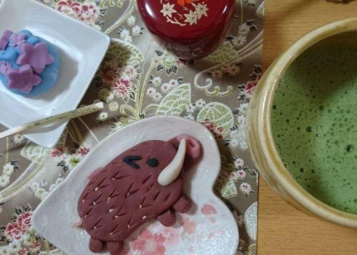 Overhead shot of a boar-shaped wagashi, a blue wagashi with purple stars, and a bowl of frothy green matcha