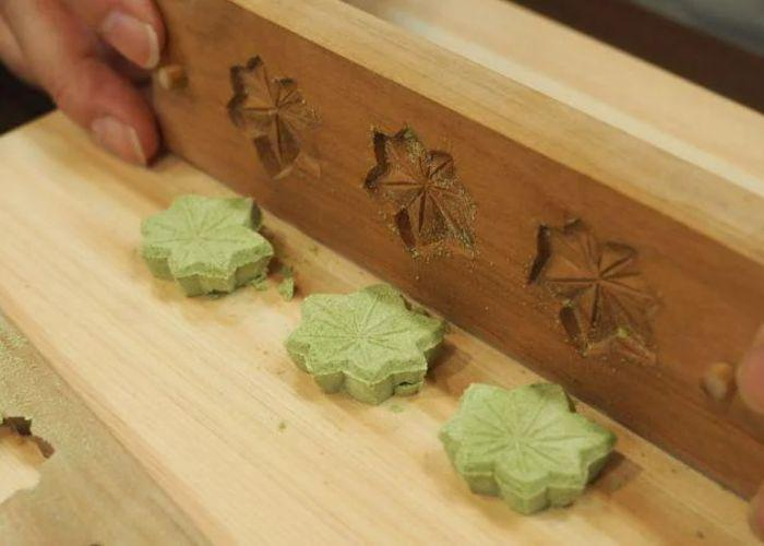 A close up image of someone popping green higashi sweets shaped like leaves out of a mold