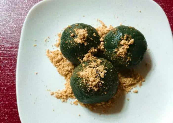A close up shot of three green mochi covered in kinako powder on a white plate