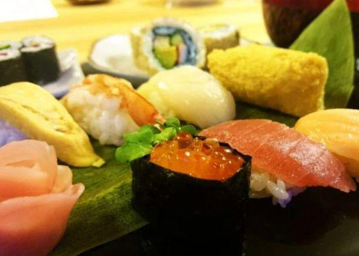 A close up shot of a plate full of different types of sushi