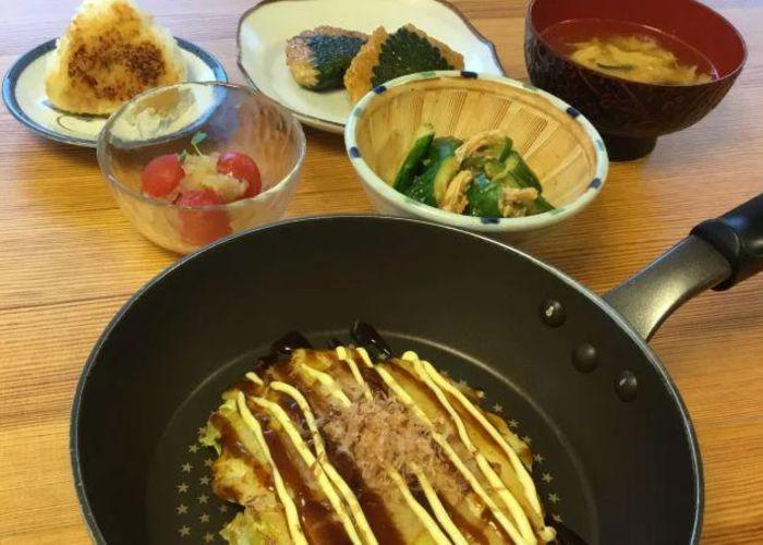 Okonomiyaki in a frying pan in the front of the shot, with several other side dishes in the background including miso soup, a rice ball and salad