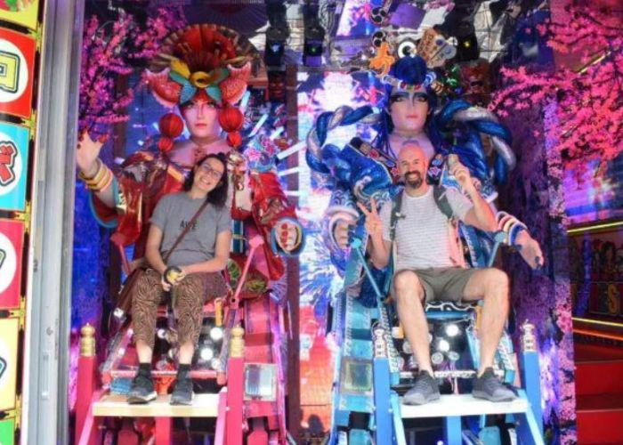 Two people in colorful neon seats with animatronic figures behind them with red and blue headpieces
