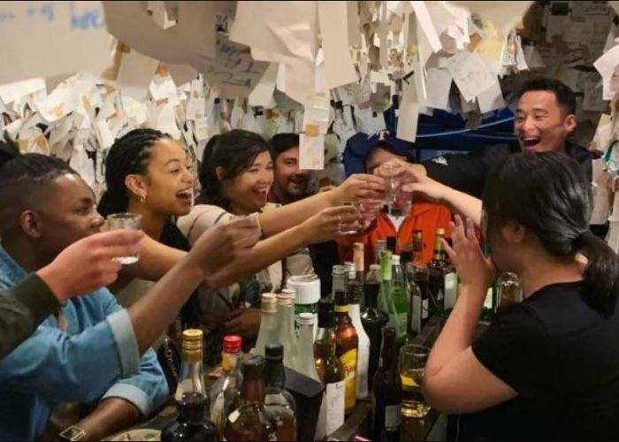 6 people and a bartender clinking glasses of beer in narrow bar with bottles of alcohol on counter