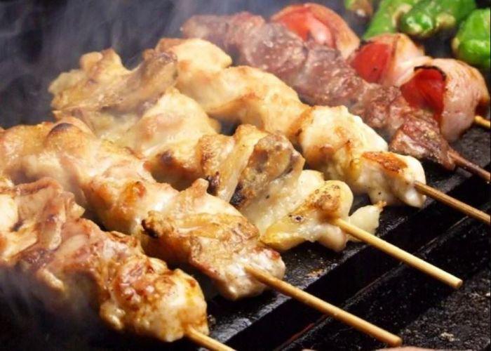 4 skewers of light meat yakitori, 2 darker red meat skewers, 1 green bell pepper skewer on grill